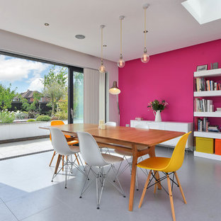Design ideas for a medium sized contemporary dining room in Other with pink walls and grey floors.