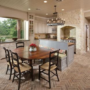 Foto di una grande sala da pranzo aperta verso la cucina mediterranea con pavimento in mattoni, pareti beige e pavimento marrone