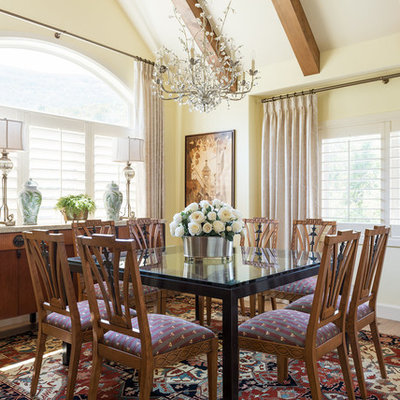 Example of a tuscan medium tone wood floor dining room design in Salt Lake City with yellow walls