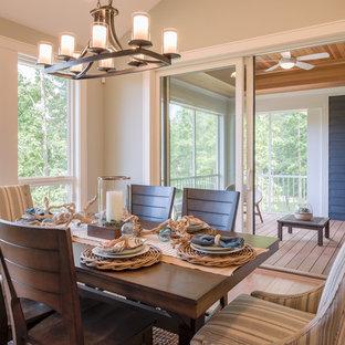 Diseño de comedor de estilo americano, de tamaño medio, abierto, con paredes grises, suelo de madera en tonos medios, chimenea de doble cara, marco de chimenea de piedra y suelo marrón