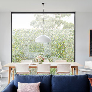 Inspiration for a contemporary open plan dining in Melbourne with white walls and grey floor.
