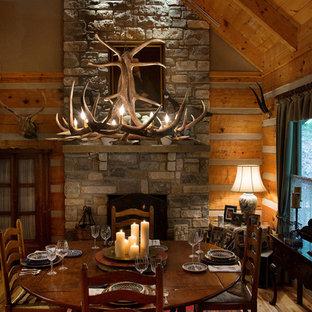 Ejemplo de comedor de cocina rústico, grande, con paredes grises, suelo de madera en tonos medios, chimenea tradicional y marco de chimenea de piedra
