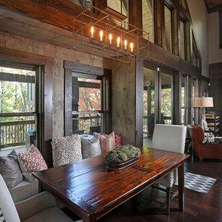 Ejemplo de comedor de estilo americano, de tamaño medio, abierto, con paredes grises, suelo de madera oscura, chimenea tradicional y marco de chimenea de madera