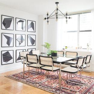 Cette photo montre une salle à manger scandinave avec un mur blanc, un sol en contreplaqué et un sol marron.
