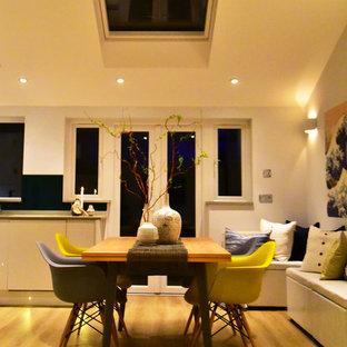 Esempio di una sala da pranzo aperta verso il soggiorno design di medie dimensioni con pareti bianche, pavimento in laminato e nessun camino