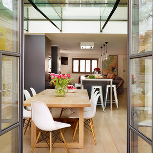 Inspiration for a large contemporary open plan dining room in London with light hardwood flooring.