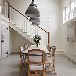 Foto di una grande sala da pranzo aperta verso il soggiorno costiera con pareti bianche e pavimento in legno verniciato