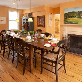 Idee per una sala da pranzo country con cornice del camino in mattoni e pareti arancioni