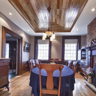 Foto di una grande sala da pranzo country chiusa con pareti grigie, pavimento in compensato, camino classico e cornice del camino in legno