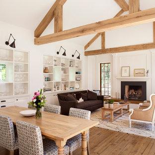 Foto di una grande sala da pranzo aperta verso il soggiorno country con pareti bianche e pavimento in legno massello medio