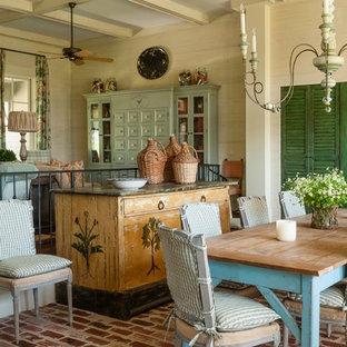 Esempio di una sala da pranzo con pareti beige e pavimento in mattoni