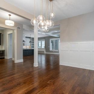 Идея дизайна: гостиная-столовая среднего размера в стиле кантри с серыми стенами, паркетным полом среднего тона, стандартным камином, фасадом камина из вагонки, коричневым полом и балками на потолке