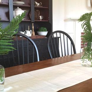Modelo de comedor de estilo de casa de campo, de tamaño medio, cerrado, con paredes blancas, suelo de madera en tonos medios, chimenea de esquina, marco de chimenea de ladrillo y suelo gris