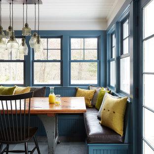Cette image montre une salle à manger ouverte sur la cuisine rustique de taille moyenne avec un mur blanc, un sol en ardoise et un sol gris.