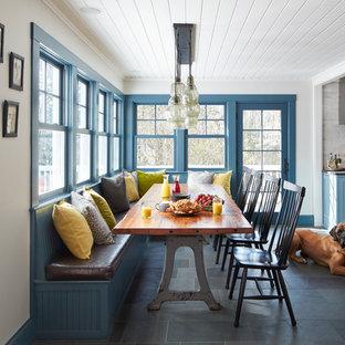 Foto di una sala da pranzo aperta verso la cucina tradizionale di medie dimensioni con pareti bianche, pavimento in ardesia e pavimento grigio