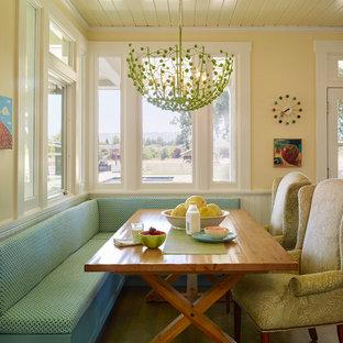 Modelo de comedor de estilo de casa de campo con paredes amarillas y suelo de madera oscura