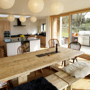 Inspiration for a medium sized farmhouse kitchen/dining room in Dorset with white walls, medium hardwood flooring and brown floors.