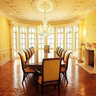 Ispirazione per un'ampia sala da pranzo aperta verso la cucina chic con pareti blu, parquet scuro, camino classico e cornice del camino in intonaco