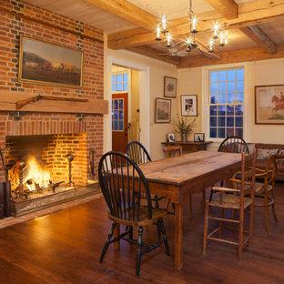 Esempio di una grande sala da pranzo aperta verso il soggiorno country con parquet scuro, camino classico, cornice del camino in mattoni e pareti gialle