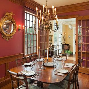 Ejemplo de comedor de estilo de casa de campo, grande, abierto, con paredes rojas, suelo de madera en tonos medios, chimenea tradicional y marco de chimenea de ladrillo