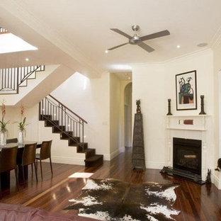 Imagen de comedor bohemio, grande, abierto, con paredes blancas, suelo de madera oscura, chimenea de esquina, marco de chimenea de metal y suelo marrón