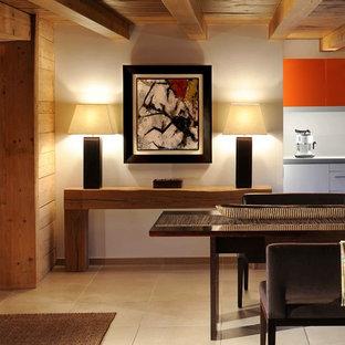 Aménagement d'une grande salle à manger ouverte sur le salon éclectique avec un mur beige et un sol beige.