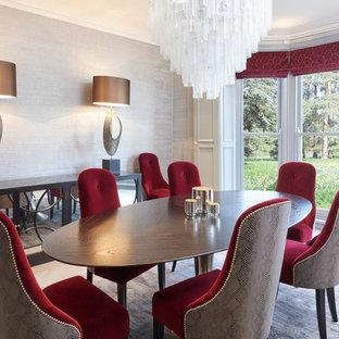 Immagine di una grande sala da pranzo minimal con pareti con effetto metallico, pavimento in legno verniciato, camino classico e cornice del camino in pietra