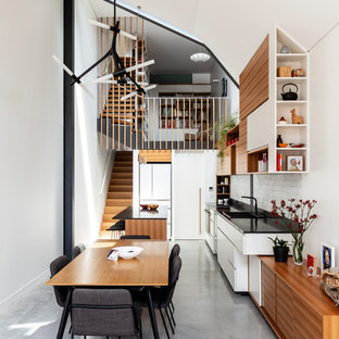 This is an example of a mid-sized contemporary dining room in Sydney with concrete floors, grey floor and white walls.