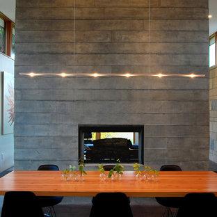 Ejemplo de comedor minimalista, de tamaño medio, abierto, con suelo de cemento, chimenea de doble cara, marco de chimenea de hormigón, paredes blancas y suelo marrón