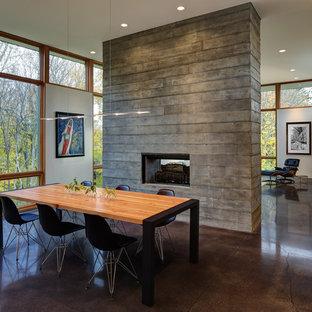Esempio di una sala da pranzo aperta verso il soggiorno contemporanea di medie dimensioni con camino bifacciale, pareti bianche, pavimento in cemento e pavimento marrone