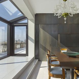 Immagine di una sala da pranzo aperta verso la cucina minimalista di medie dimensioni con pareti bianche, parquet chiaro, nessun camino e pavimento bianco
