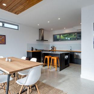 Diseño de comedor de cocina actual con paredes blancas, suelo de cemento y suelo gris