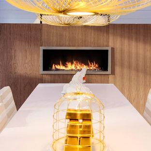 Imagen de comedor de cocina bohemio con chimenea lineal, marco de chimenea de madera y paredes blancas