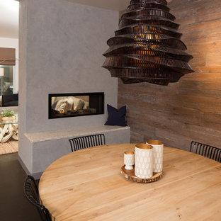 Foto de comedor actual, grande, abierto, con paredes marrones, suelo de cemento, chimenea de doble cara, marco de chimenea de hormigón y suelo gris