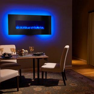 Inspiration pour une salle à manger bohème fermée et de taille moyenne avec un mur beige, un sol en bois brun, cheminée suspendue et un manteau de cheminée en métal.