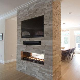 ニューヨークの大きいトランジショナルスタイルのおしゃれなダイニングキッチン (ベージュの壁、淡色無垢フローリング、両方向型暖炉、石材の暖炉まわり) の写真