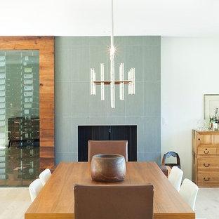 Foto di una sala da pranzo aperta verso il soggiorno minimal di medie dimensioni con parquet chiaro, cornice del camino piastrellata, pareti grigie e camino classico