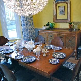 This is an example of a traditional dining room in Other with yellow walls and medium hardwood flooring.