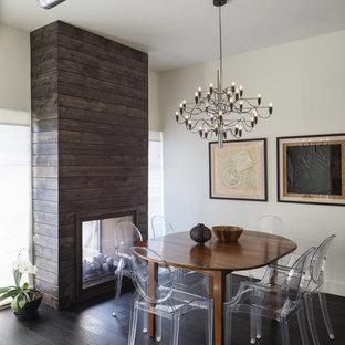 Aménagement d'une salle à manger contemporaine avec un mur blanc, un sol en bois foncé, une cheminée double-face et un manteau de cheminée en bois.