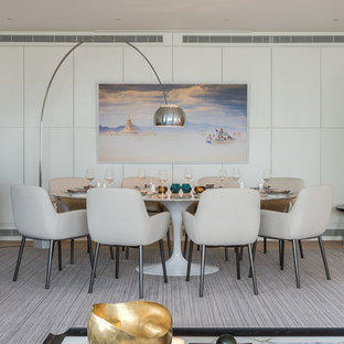 This is an example of a contemporary dining room in London with white walls, light hardwood flooring and beige floors.