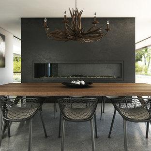 Bild på en stor funkis matplats, med betonggolv, en spiselkrans i gips och svarta väggar