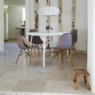 Immagine di una sala da pranzo aperta verso il soggiorno contemporanea di medie dimensioni con pareti bianche e pavimento in pietra calcarea