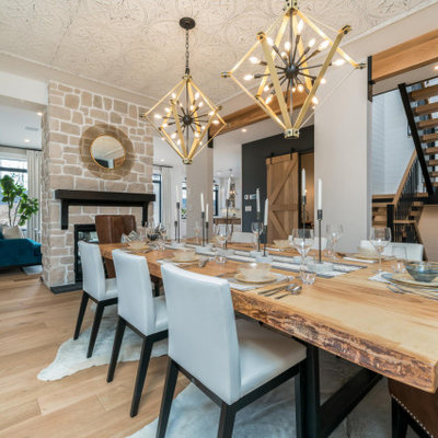 Large cottage light wood floor kitchen/dining room combo photo in Toronto with white walls, a standard fireplace and a stone fireplace