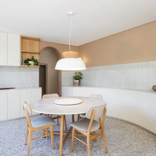 Aménagement d'une salle à manger ouverte sur la cuisine contemporaine de taille moyenne avec un mur orange et un sol gris.