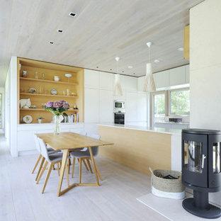 Inredning av ett modernt stort kök med matplats, med vita väggar, en öppen vedspis, en spiselkrans i metall och grått golv