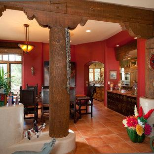 Immagine di un'ampia sala da pranzo stile americano con pareti rosse e pavimento in cemento