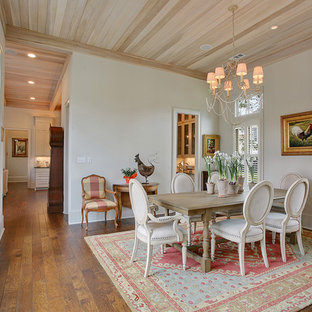 Example of a mid-sized farmhouse dark wood floor enclosed dining room design in New Orleans with white walls and no fireplace