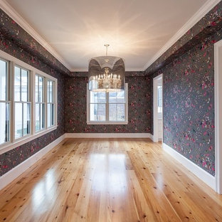 Example of a farmhouse light wood floor and brown floor enclosed dining room design in DC Metro with multicolored walls