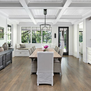 This is an example of a large nautical dining room in Detroit with medium hardwood flooring, no fireplace and white walls.
