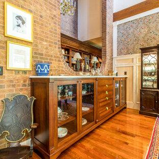 デンバーの広いトラディショナルスタイルのおしゃれな独立型ダイニング (茶色い壁、無垢フローリング、両方向型暖炉、レンガの暖炉まわり、赤い床) の写真